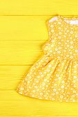 Baby-girl Yellow Printed Top. Infant Girl Yellow Patterned Dress On Yellow Wooden Background. Toddle poster