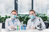 Scientific Researchers In Goggles And Medical Masks Sitting At Workplace With Reagents In Tubes And  poster
