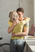 Affectionate Couple Standing And Hugging At Home poster