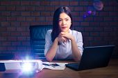 Young Attractive And Successful Asian Executive Woman Watching Presentation Projected On Screen In H poster