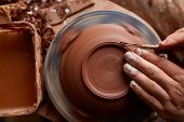 Adult Male Potter Master Modeling The Clay Plate On Potters Wheel. Top View, Closeup, Hands Only. poster