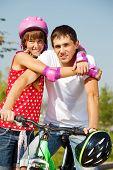 Постер, плакат: Портрет Веселые девушки в защитные спортивной одежды и ее отец на велосипеде