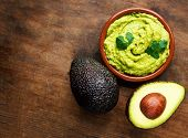 Avocado With Guacamole Sauce On A Dark Wood Background. Half And Whole Avocadoes Close Up. Top View. poster