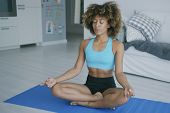 Fit ethnic woman in sportswear sitting on mat at home and meditating in yoga pose breathing and keep poster