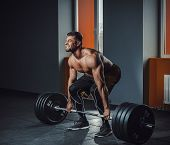 European Caucasian Athletic Man Doing Deadlift With Heavy Barbell. Man Lifting Barbell Opposite Wind poster