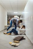 Schoolboy Being Bullied By Classmate In School Corridor Under Lockers While Other Boy Running To Hel poster