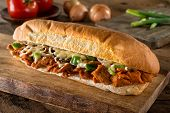 A Delicious Spicy Barbecue Pork Submarine Sandwich On A Rustic Wood Table Top. poster