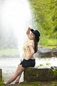smiling woman sitting at pond
