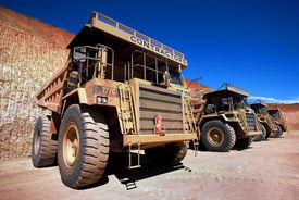 stock photo of dump_truck  - row of dump trucks at open cut gold mine  - JPG