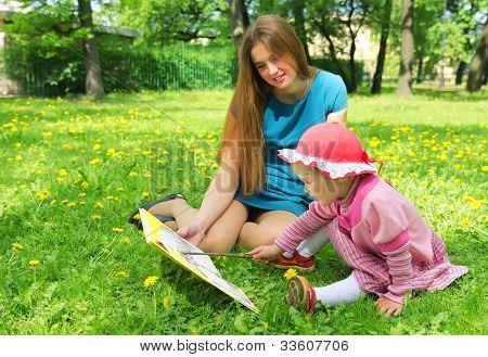 Mädchen und Mutter liest das Buch Frühlingspark