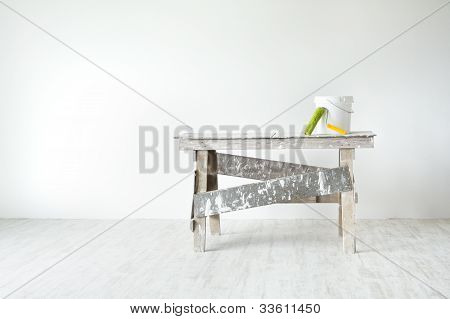 Construction Grunge Ladder, Paint Roller And Paint Bucket In White Interior: White Wall And Gray Flo