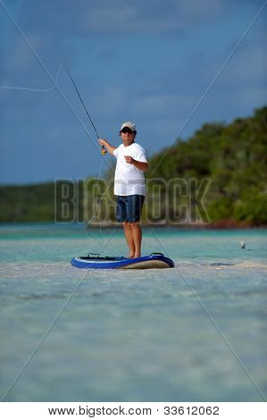 Man Fly Fishing On A Paddle Board