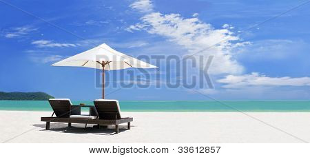 panoramic view ow the tropical beach with umbrella and two beds