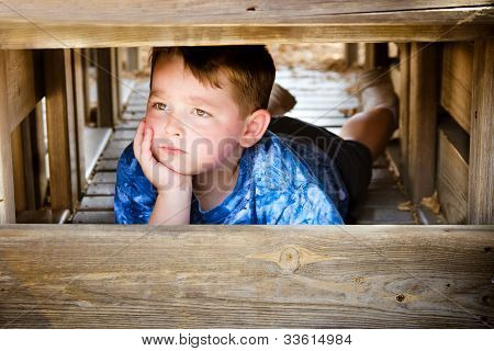 Unhappy child hiding and sulking while playing on playground