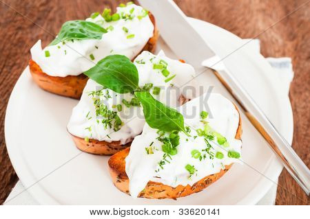 Toasted Baguette Slice With Ricotta And Herbs On White Plate