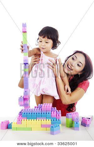 Chica con madre jugando con bloques