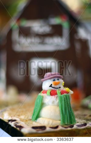 Snowman In Front Of Ginger Bread House