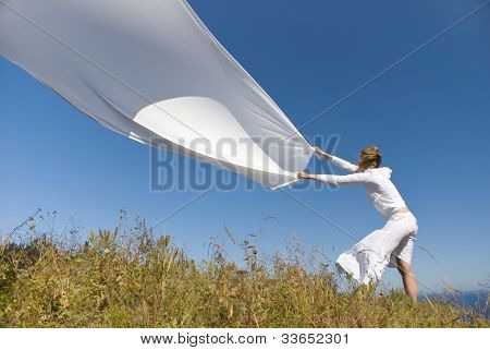 Girl In White Dress With Fabric In Hands In The Wind