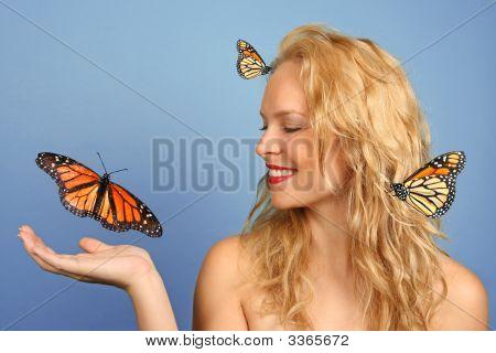 Mujer con muchas mariposas en la mano y su pelo