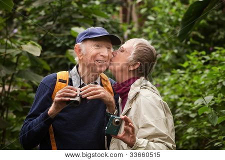 Mature Couple Kissing In Woods