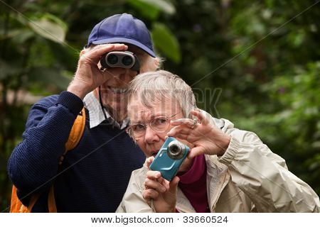 Couple Using Camera And Binoculars