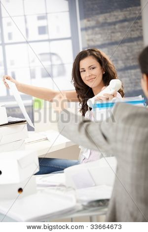 Joyous female office worker passing phone to colleague in office, smiling.
