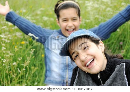 cute arabic  little girls smiling in a park close-up