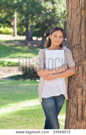 Smiling young woman holding a laptop while leaning against a tree