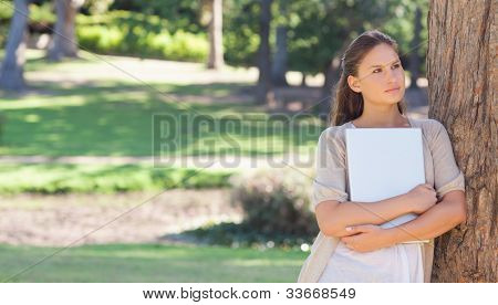 Young woman holding a laptop while leaning against a tree