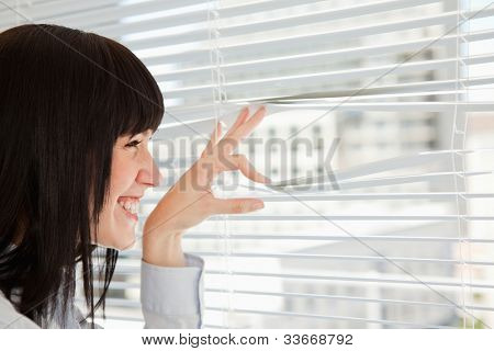 A woman smiles as she looks out through her window blinds