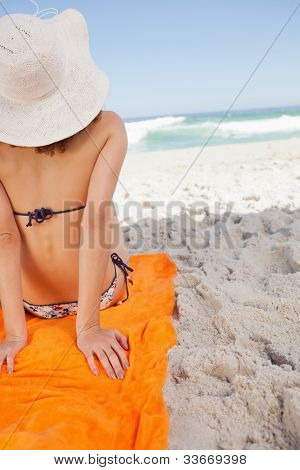Rear view of a woman sunbathing while sitting on a beach towel in front of the sea