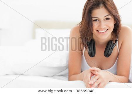 A woman at the end of the bed with headphones around her neck, she is smiling while looking forward.