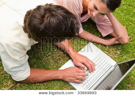Elevated view of two friends smiling while using a laptop together as they lie down on the grass