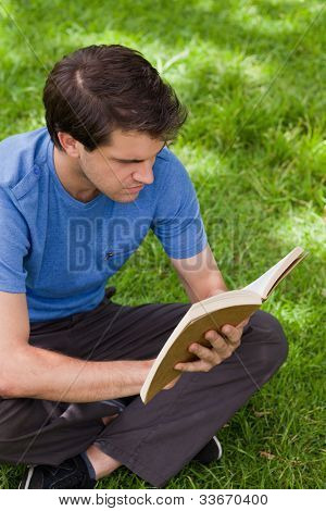 Young serious man sitting cross-legged on the grass in a park while reading a book