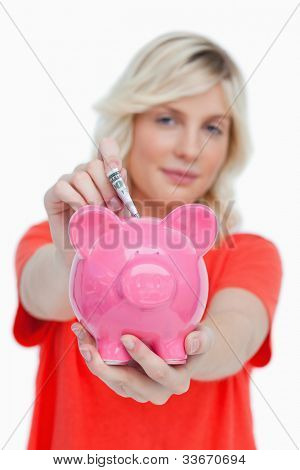 Piggy bank held by a woman and receiving notes against a white background