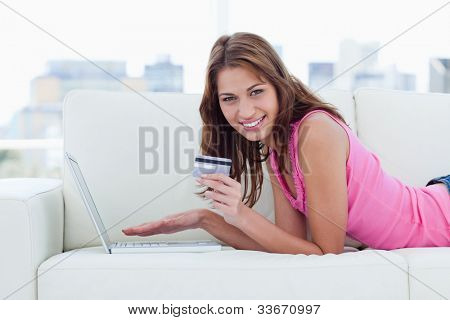 Young woman showing a beaming smile while holding a grey credit card