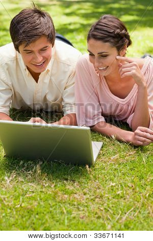 Two friends smiling while using a laptop together as they lie down in the grass