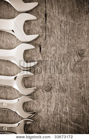 metal nuts and wrench tool on wood background texture