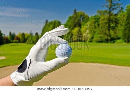 mão mostrando a bola de golfe sobre bancas de areia no belo campo de golfe com céu azul