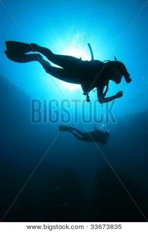 Scuba Diving in the Ocean: Silhouettes against sunburst