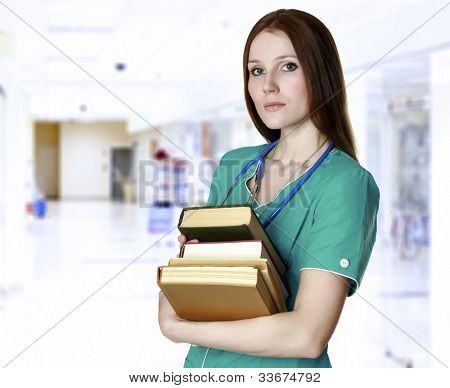 Pretty nurse or doctor with books in a corridor of a hospital or medical college