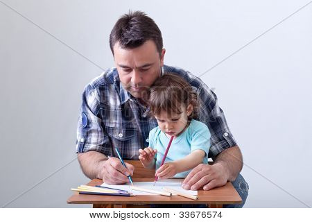 Toddler boy drawing with colored pencils aided by his father