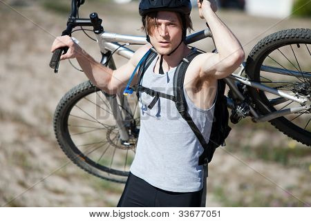 Young man carrying his mountain bike