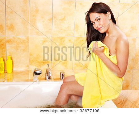 Young woman undressing in bathroom