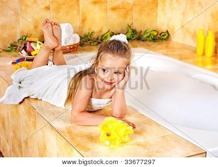 Little girl relaxing in bubble bath .