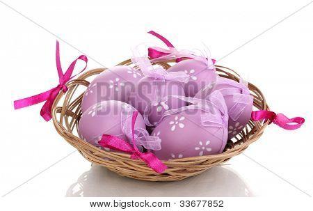 Coloridos huevos de Pascua en cesta aislado en blanco