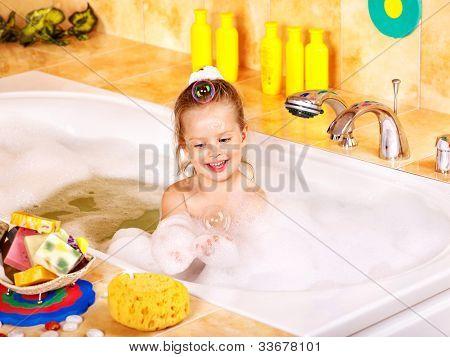 Happy child soaking in bubble bath .