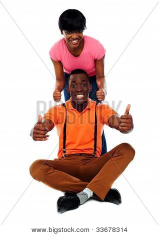 Couple Showing Double Thumbs-up To Camera