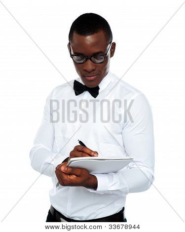Confident Young Man Writing On Notepad