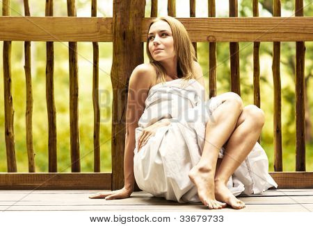 Young woman relaxing outdoor, sexy female sitting on the tropical terrace wrapped in bed sheet, calm pretty girl enjoying spa hotel resort, sensual shy romantic lady, vacation and health care concept